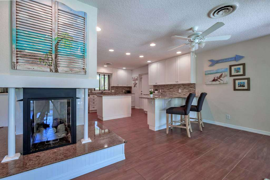 Open Floor Plan with Wrap Around Fireplace to Kitchen